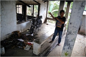 An activist, shows a firebombed building at the church sheltering displaced Lumads