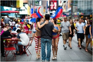 Paola Peña, left, and Mey Ovalles, topless and covered in body paint, pose for a photo in Times Square.